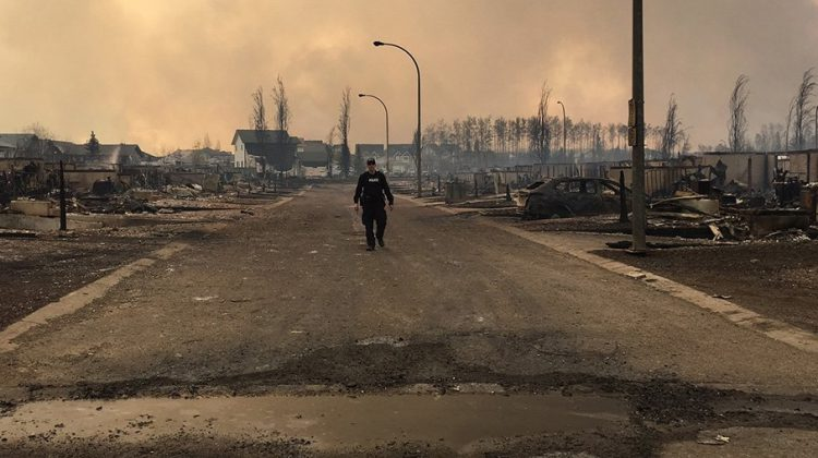 A mountie surveys the damage on a street in Fort McMurray, RCMP Alberta