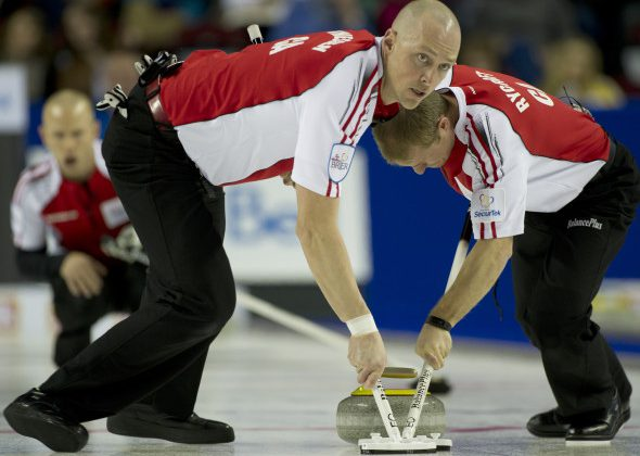 Nolan Thiessen, left, and Carter Rycroft sweep Pat Simmons' rock during the 2015 Tim Hortons Brier in Calgary. (Photo, Curling Canada/Michael Burns)